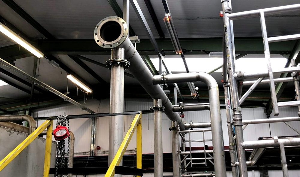 Stainless steel pipework being installed inside a building