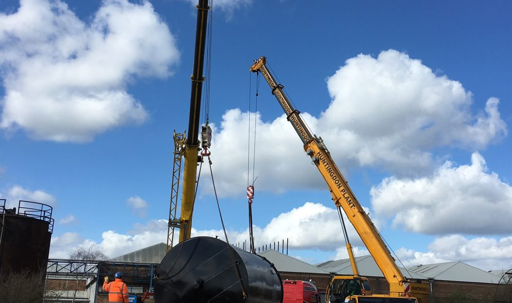 Two cranes lifting large black tank from a lorry
