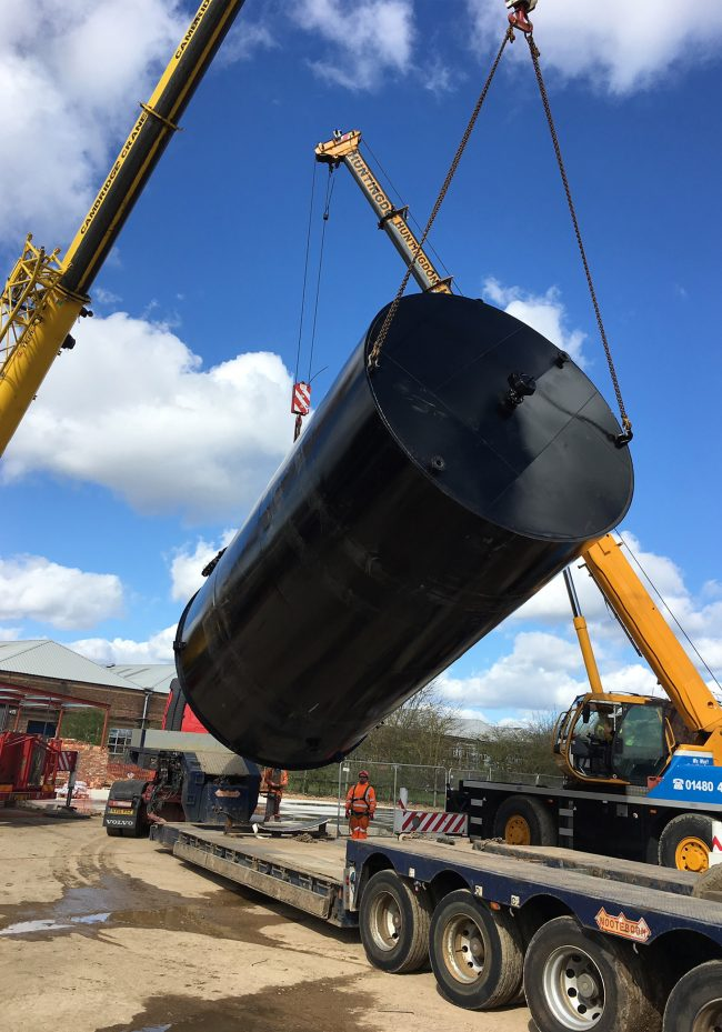 Two cranes lifting large black effluent tank from a lorry