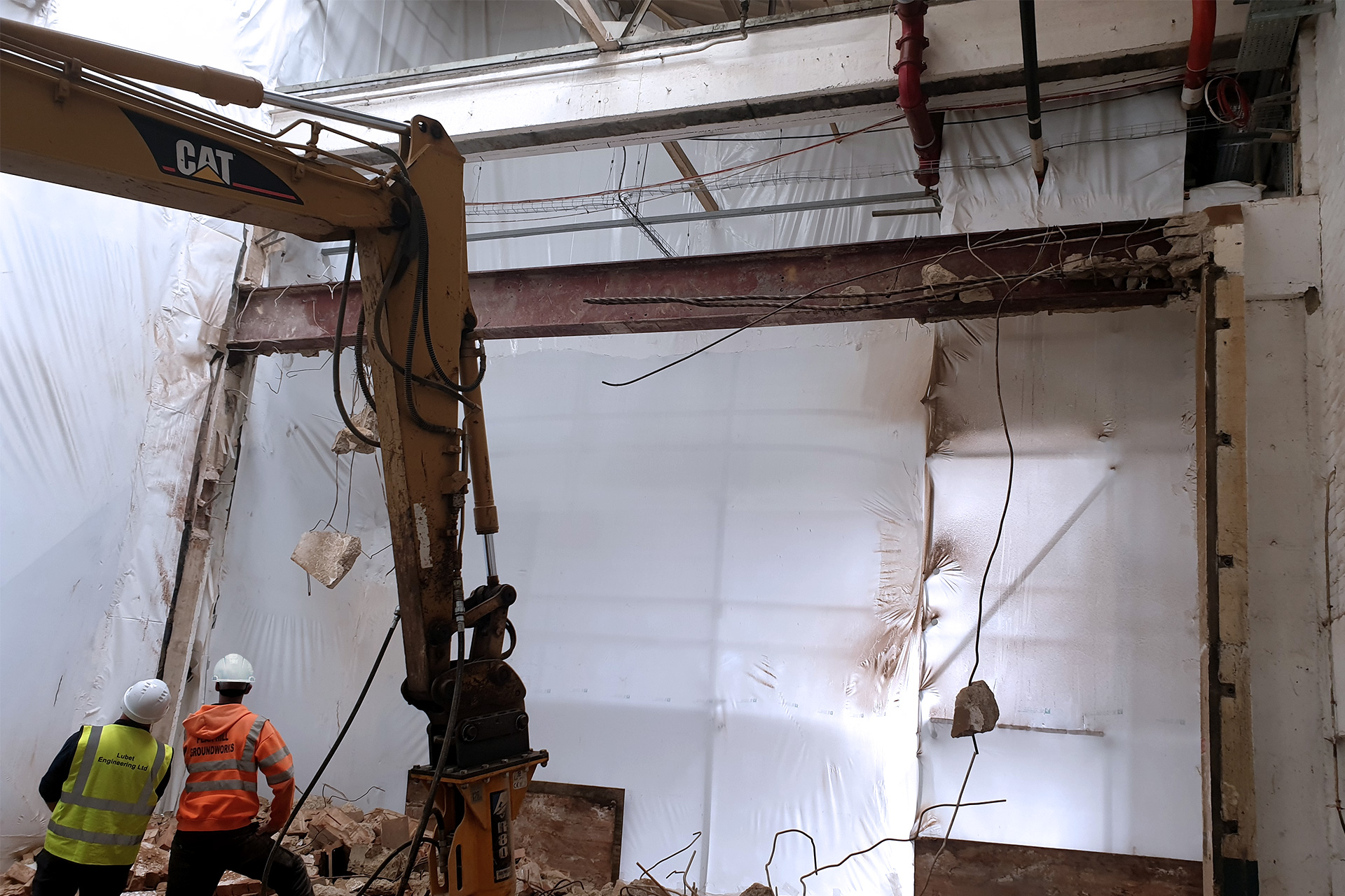 Two workers and an excavator demolishing concrete