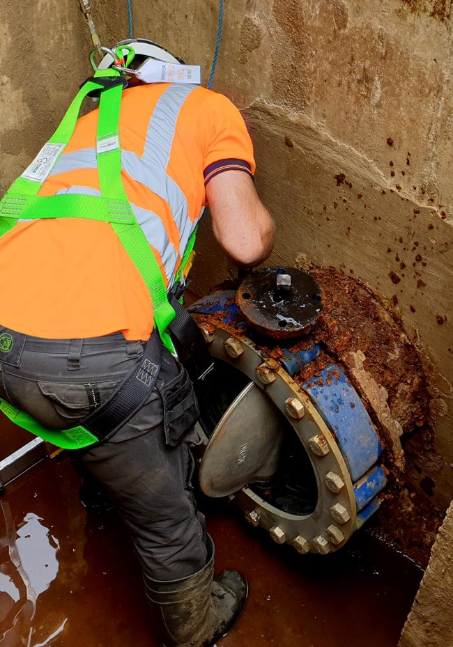 Construction worker working on an underground isolation valve