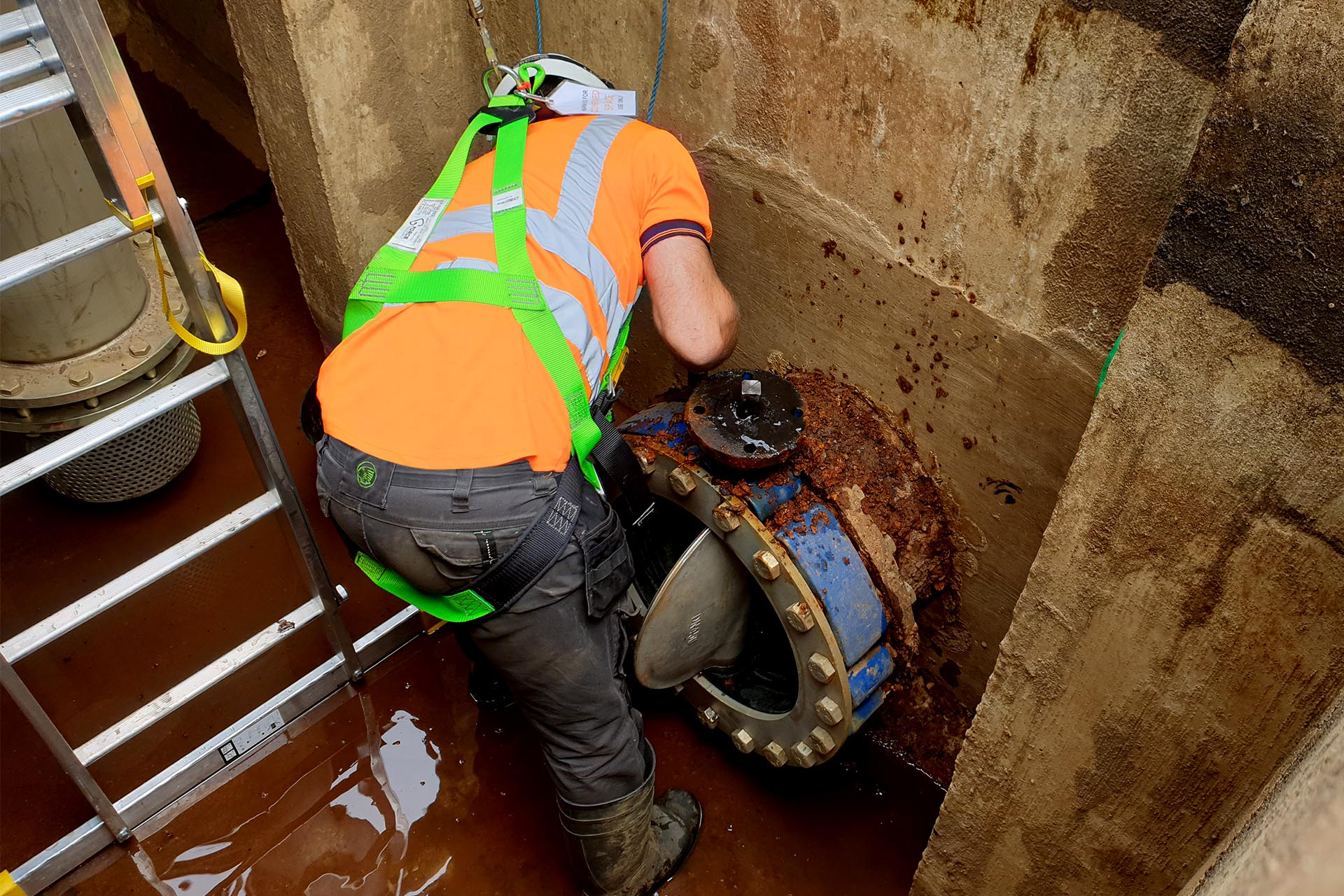 Construction worker working on an underground isolation valve