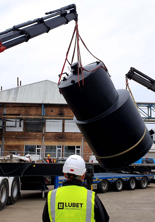 Large black bulk storage tank being lifted from a lorry