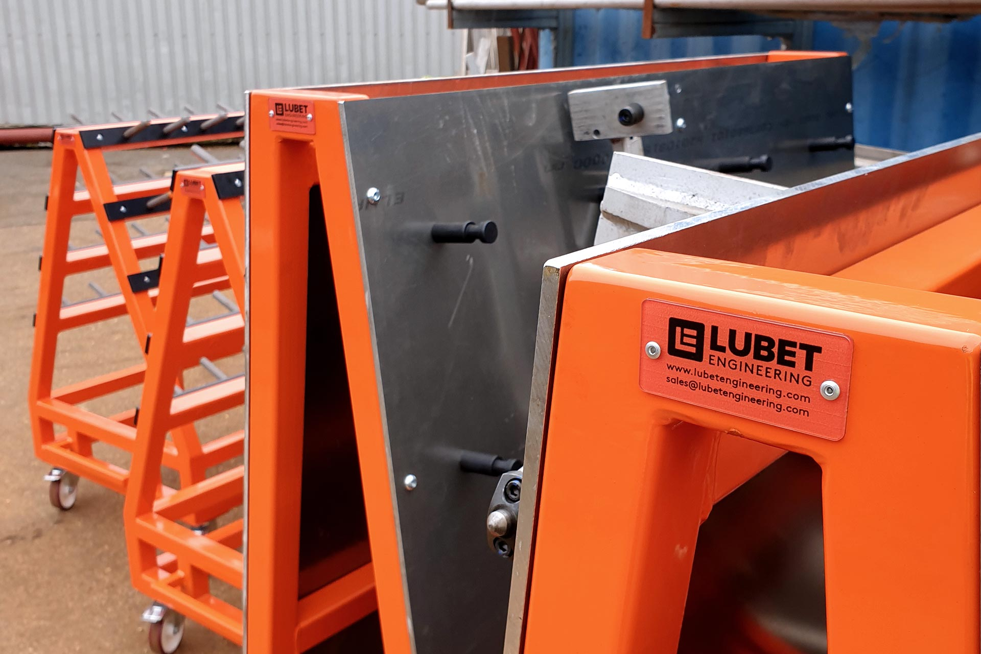 Close up view of four orange parts trolleys lined up