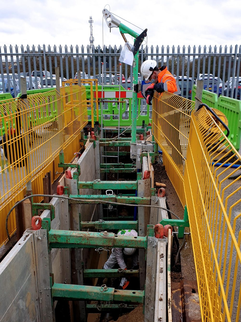 Man looking into a trench with safety barriers