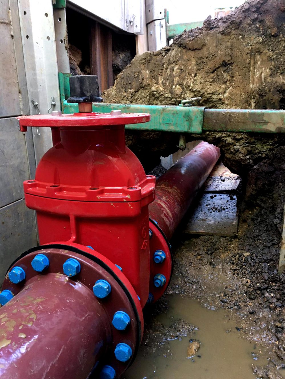 Red sprinkler valve and pipe inside a trench