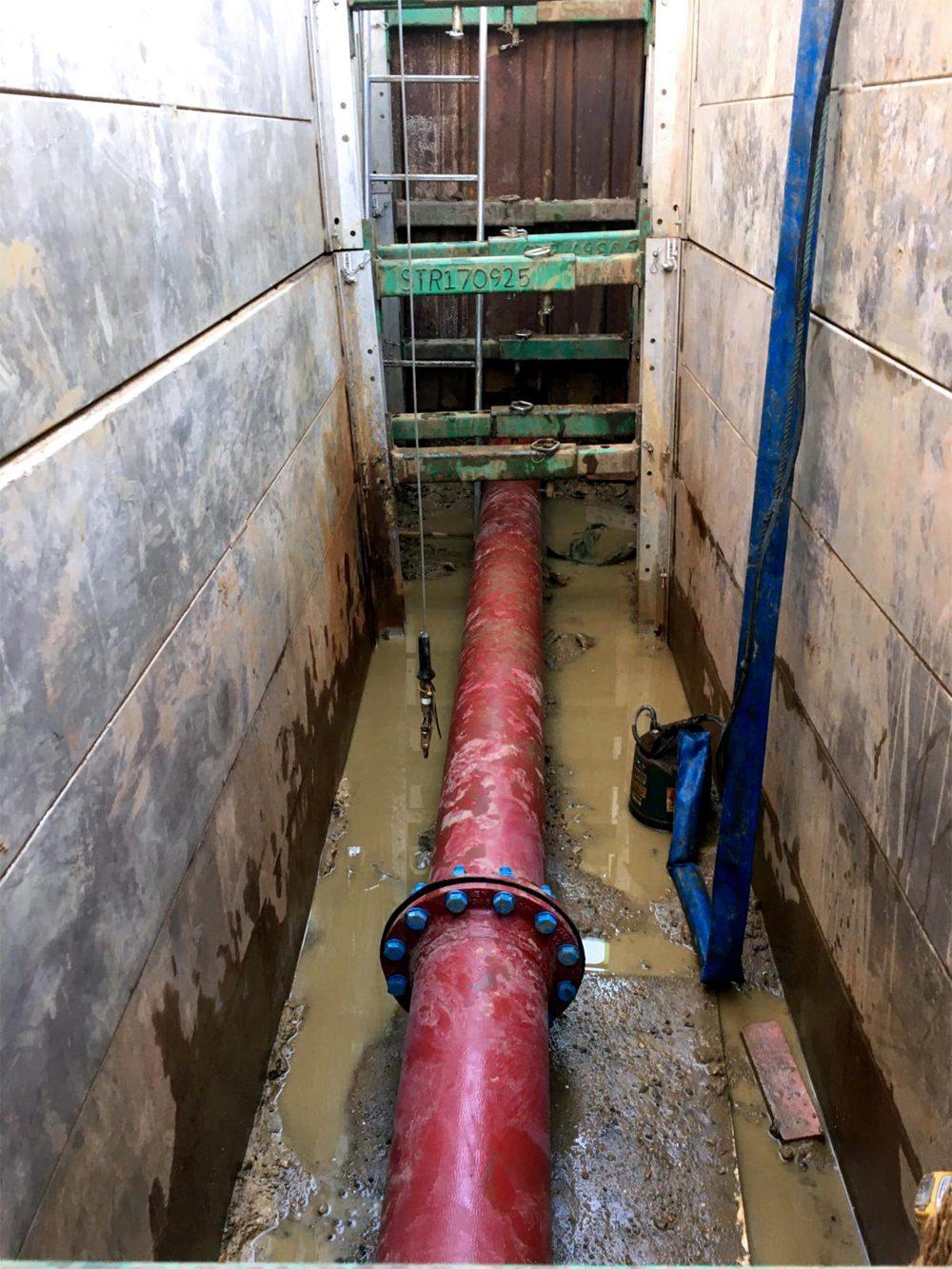 Red sprinkler pipe inside a shored trench